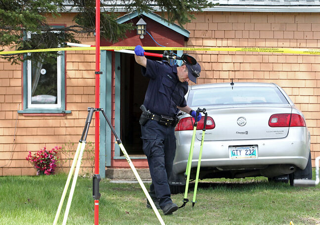 An RCMP officer works at the scene of a suspicious death in MacGregor on Monday afternoon.