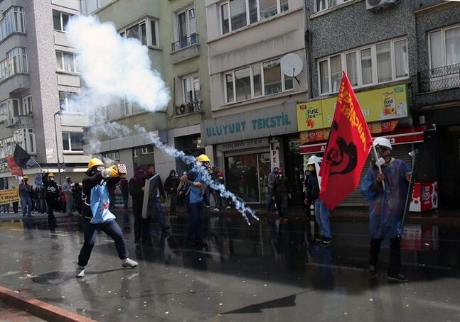 Protesters stand as riot police use water cannons and teargas to disperse thousands of people trying to reach the city's main Taksim Square to celebrate May Day in Istanbul, Turkey, Thursday, May 1, 2014. Clashes erupted between May Day demonstrators and riot police as crowds determined to defy a government ban tried to march to the city's iconic Taksim Square. Security forces pushed back demonstrators with water cannons and tear gas. (AP Photo/Emrah Gurel)