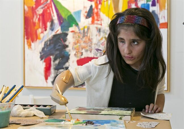 FILE - In this April 2, 2014, file photo, Afghan war victim Shah Bibi Tarakhail uses her new prosthetic arm to paint at Galerie Michael in Beverly Hills, Calif. Seven-year-old Tarakhail whose love of painting won the hearts of U.S. doctors who fitted her with a prosthetic arm is returning to the United States after her newfound celebrity made her a subject of death threats in her homeland. Tarakhail is scheduled to arrive at Los Angeles International Airport on Thursday, June 18, 2014 on the last leg of a journey from Kabul. Tarakhail lost her right arm when she picked up a grenade following a firefight between U.S. and Taliban forces in her village. (AP Photo/Damian Dovarganes, File)
