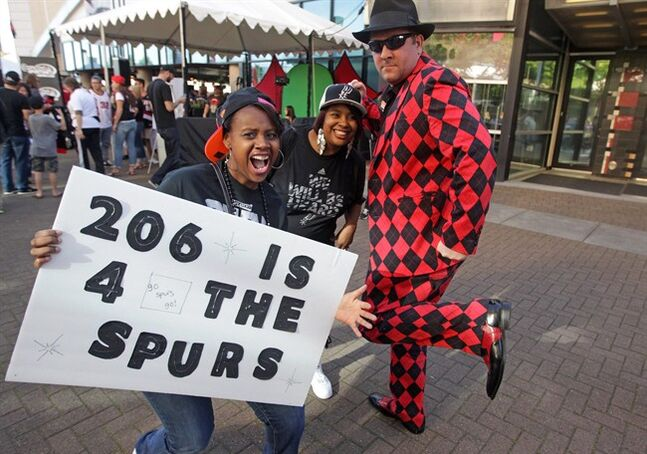 San Antonio Spurs fans Nicol Mack, left, Shantae Duckworth, center, pose for a photo with Portland Trail Blazers fan Scott Cummins before Game 4 of a Western Conference semifinal NBA basketball playoff series Monday, May 12, 2014, in Portland, Ore. (AP Photo/Rick Bowmer)