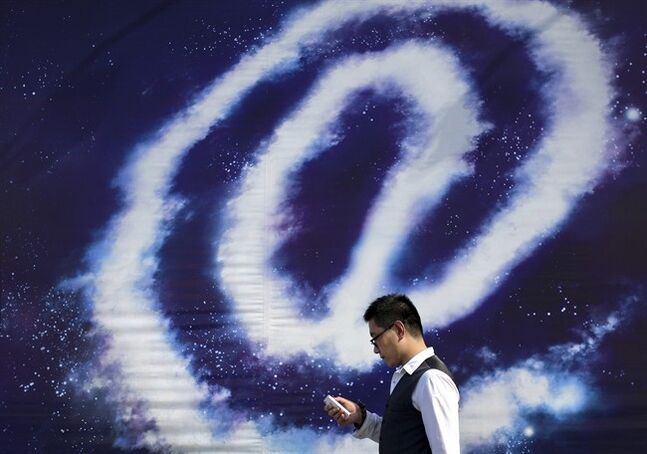 A Chinese man checking on his smartphone walks past an