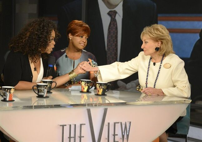 This Thursday, May 15, 2014 photo released by ABC shows, Oprah Winfrey, left, grasping hands with Barbara Walters, right, as co-host Sherri Shepherd looks on during a taping of Walters' final co-host appearance on