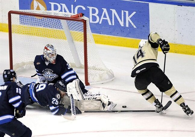 St John's IceCaps' Jordan Hill (29) collides with his goalie, Michael Hutchinson (33), while blocking a shot from Wilkes-Barre/Scranton Penguins' Tom Kuhnhackl (14) during the first period of Game 3 of the AHL Eastern Conference semifinal hockey series, Wednesday, May 28, 2014, in Wilkes-Barre, Pa. The Winnipeg Jets are keeping their American Hockey League farm team in St. John's, N.L., at least to the end of the 2015-'16 season. THE CANADIAN PRESS/AP/The Citizens' Voice, Mark Moran)