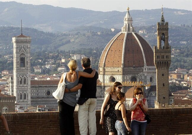 In this photo taken on July 8, 2013 a couple looks at the Florence Santa Maria del Fiore Basilica, with Giotto's bell tower, left, Brunelleschi's dome, from Forte Belvedere, Italy. Kim Kardashian and Kanye West will get married at Florence's imposing 16th century Belvedere Fort on May 24, a spokeswoman at the Florence mayor's office said Friday, May 16, 2014. The couple rented the fort, located next to Florence's famed Boboli Gardens, for 300,000 euros ($410,000). Di Lupo said a Protestant minister will preside, spokeswoman Elisa Di Lupo said. The 36-year-old rapper proposed to the reality star on her 33rd birthday in October 2013 renting out San Francisco's AT&T Park for the occasion. There has been no explicit confirmation from either Kardashian or West. In an email Thursday to The Associated Press, Kardashian's representative Ina Treciokas said she wasn't able to comment on reports about the nuptials. (AP Photo/Francesco Bellini)