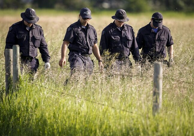 Police investigators comb a hay field north of Airdrie, Alta., Saturday, July 5, 2014, looking for clues to the disappearance of three people. THE CANADIAN PRESS/Jeff McIntosh