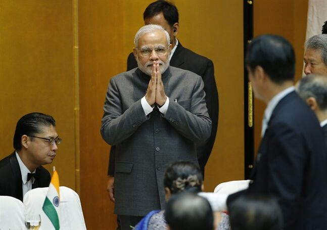 Indian Prime Minister Narendra Modi greets business leaders upon his arrival at the hall at the Japan Business Federation for luncheon in Tokyo Monday, Sept. 1, 2014. Japanese government and business leaders are pledging support for Indian Modi's effort to modernize his country's economy. Modi was on an official visit to Japan. (AP Photo/Koji Sasahara)