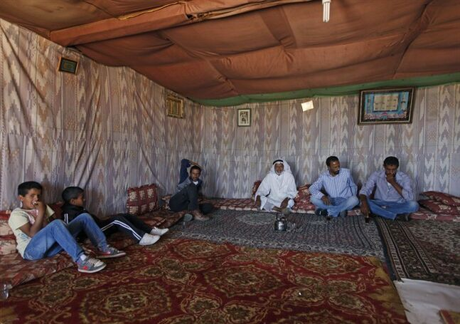 In this May 1, 2014 photo, Palestinian bedouins rest inside a tent donated by the European Union, in the Palestinian Bedouin community Jabal al-Baba, east of Jerusalem. The EU has expressed concern and criticized Israel for dismantling three EU-funded trailer homes in Jabal al-Baba and issuing final demolition orders for an additional 18. In all, EU-funded aid agencies have distributed some 200 trailers, latrines and water tanks to Bedouin communities in the Jerusalem area. (AP Photo/Majdi Mohammed)