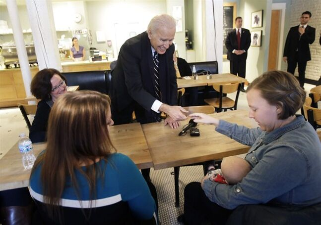 Vice President Joe Biden greets women who have either signed up for coverage or have helped others sign up for insurance under the federal health care law during a stop at Moose and Sadie's coffee shop Wednesday, Feb. 19, 2014, in Minneapolis. (AP Photo/Jim Mone, Pool)
