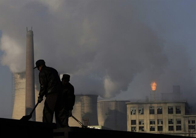 FILE - In this Nov. 30, 2007 file photo, backdrop by cooling towers of a power plant and chemical factory, miners shovel coal at a mine in Xiahuayuan county, north China's Hebei province. President Barack Obama's proposal to curb U.S. greenhouse gas emissions might improve the chances of completing a global climate treaty but is unlikely to defuse demands by China, India and others for Americans to do more. China, the biggest emitter, has promised to curb its output but with its economy slowing, and communist leaders under pressure to generate jobs, has resisted binding limits. (AP Photo/Oded Balilty, File)