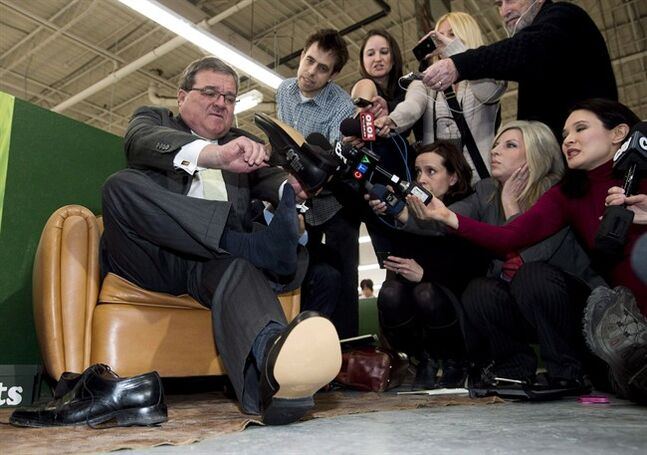 Finance Minister Jim Flaherty puts on his annual pre-budget shoes at the Roots Leather Factory in Toronto on Wednesday, March 20, 2013. Flaherty has sometimes warned Canadians there's no free lunch, but on budget day next week he'll be paying for hundreds of them. THE CANADIAN PRESS/Nathan Denette