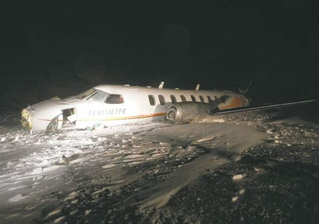 A damaged Fairchild Metro 3/23 aircraft lies in the snow at the Sanikiluaq, Nunavut airport on Saturday. The RCMP say a chartered Perimeter Aviation flight from Winnipeg with nine people on board crashed Saturday shortly after 6 p.m., killing a six-month-old baby boy. Eight survivors are being treated for non-life-threatening injuries.