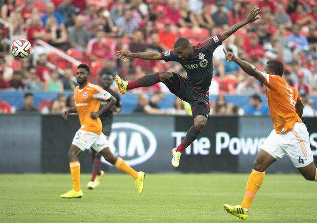 Toronto FC's Jermain Defoe, centre, leaps for a ball during the first half of MLS soccer action against the Houston Dynamos in Toronto on Saturday, July 12, 2014. THE CANADIAN PRESS/Darren Calabrese