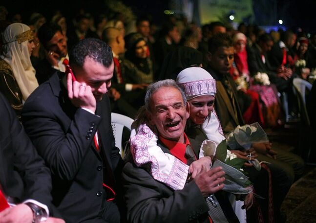Palestinian couples are pictured, during a mass wedding ceremony, in the West Bank city of Jericho, Tuesday, Jan. 28, 2014. 218 Palestinian couples attended a mass wedding in the parking lot of a five-star hotel. (AP Photo/Nasser Shiyoukhi)