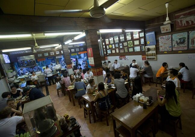 In this Wednesday, Aug. 13, 2014 photo, customers fill the interior Thip Samai restaurant in Bangkok, Thailand. Thip Samai's menu consists of eight types of Pad Thai. The traditional version costs 50 baht ($1.50). (AP Photo/Sakchai Lalit)