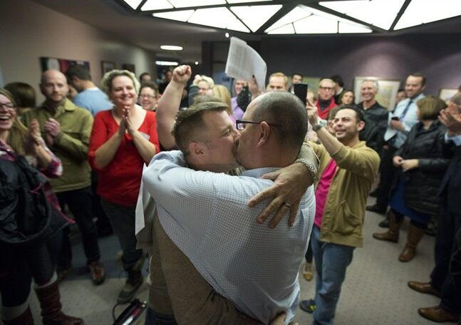 FILE - In this Dec. 20, 2013, file photo, Chris Serrano, left, and Clifton Webb kiss after being married, as people wait in line to get licenses outside of the marriage division of the Salt Lake County Clerk's Office, in Salt Lake City. Utah is appealing a federal judge's ruling that officials must recognize gay marriages that took place in the state after a same-sex marriage ban was overturned. Utah Gov. Gary Herbert and Attorney General Sean Reyes filed an appeal Wednesday, June 4, 2014, sending the case to the Denver-based 10th Circuit Court of Appeals. (AP Photo/Kim Raff, File)