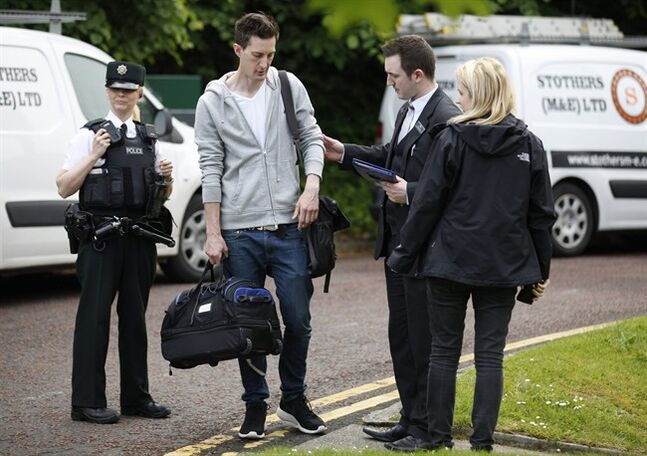 Members of staff and police help guests leave the Everglades Hotel, Londonderry, Northern Ireland, Friday, May 30, 2014. A masked man has thrown what police have described as a
