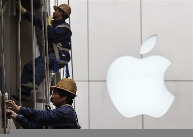 Workers clean windows near Apple's retail store in Beijing, China on April 10, 2014. THE CANADIAN PRESS/AP, Andy Wong