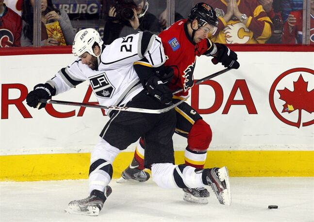 Los Angeles Kings' Dustin Penner, left, tangles with Calgary Flames' Chris Butler during third period NHL hockey action in Calgary, Alta., Wednesday, Feb. 20, 2013. The Los Angeles Kings beat the Calgary Flames 3-1. THE CANADIAN PRESS/Jeff McIntosh
