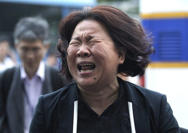 A family member of passengers aboard the sunken ferry Sewol cries after a pretrial hearing of crew members of the ferry at Gwangju District Court in Gwangju, South Korea, Tuesday, June 10, 2014. Hostile spectators cursing, shouting and weeping behind them, 15 crew members from the sunken South Korean ferry appeared in court Tuesday to enter pleas on charges of negligence and failing to save more than 300 dead or missing passengers. (AP Photo/Ahn Young-joon)