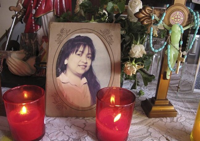 In this Monday, July 21, 2014 photo, candles are lit next to a portrait of Irene Gunawan, one of three Filipinos who died in the Malaysia Airlines Flight 17 downed over in eastern Ukraine, on an improvised altar prior to a novena prayer at her clan residence at Pagbilao township, Quezon province south of Manila, Philippines. Irene, her two children and her Indonesian husband Budy, were killed along with 294 others onboard the flight. (AP Photo/Jim Gomez)