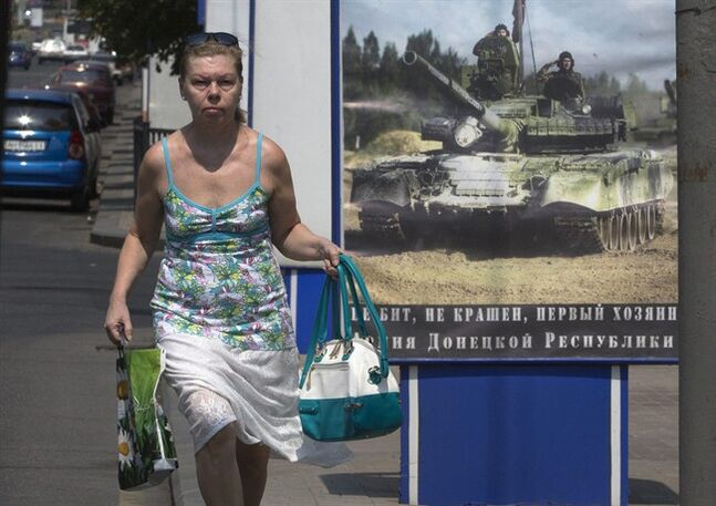 A woman walks past a poster calling for military recruits to the separatist forces in the city of Donetsk, eastern Ukraine Monday, Aug. 4, 2014. The Interfax news agency reported Monday that Russia's air force began week-long military drills in the central and western regions of Russia, a move that could spark further fears that Moscow is ready to flex its military muscle in Ukraine. (AP Photo/Dmitry Lovetsky)