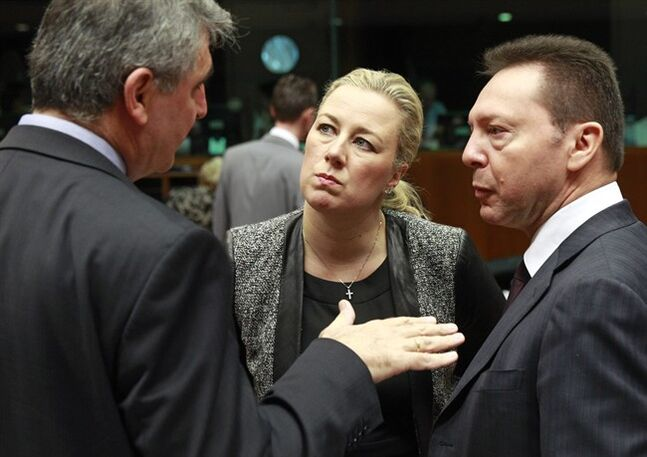 Greek Finance Minister and President of the rotating EU Council Yannis Stournaras, right, talks with Finnish Finance Minister Jutta Urpilainen, center, and an unidentified delegation member prior to the start of the EU finance ministers meeting at the European Council building in Brussels Tuesday, Feb. 18, 2014. (AP Photo/Yves Logghe)