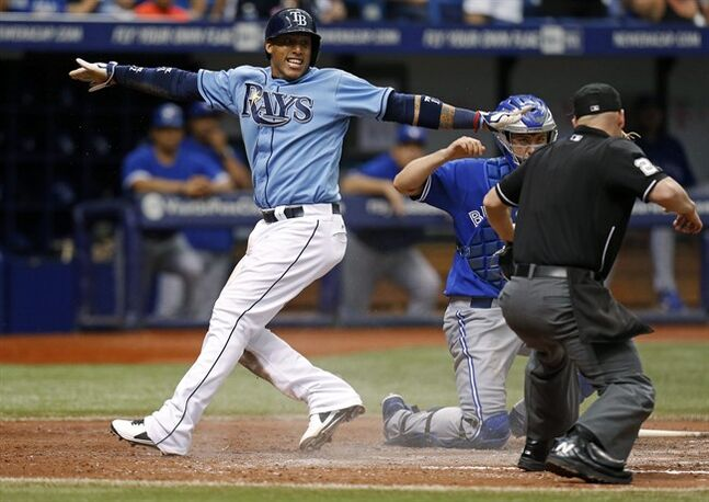 Tampa Bay Rays' Yunel Escobar motions he is safe after sliding into home against Toronto Blue Jays catcher Josh Thole as umpire Sean Barber begins to call him out during the sixth inning of a baseball game Sunday, July 13, 2014, in St. Petersburg, Fla. Barber called Escobar out, but the call was reversed after video review. (AP Photo/Mike Carlson)