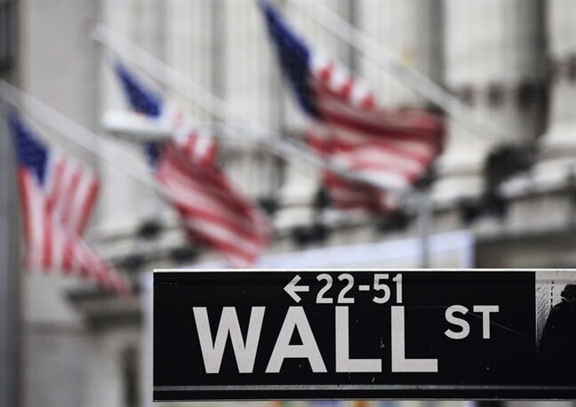 FILE - This file photo made April 22, 2010 shows a Wall Street sign in front of the New York Stock Exchange. U.S. stock futures slipped Wednesday, June 11, 2014, after the World Bank downgraded its forecast for the global economy this year, citing a bitter American winter and the political crisis in Ukraine. (AP Photo/Mark Lennihan, File)