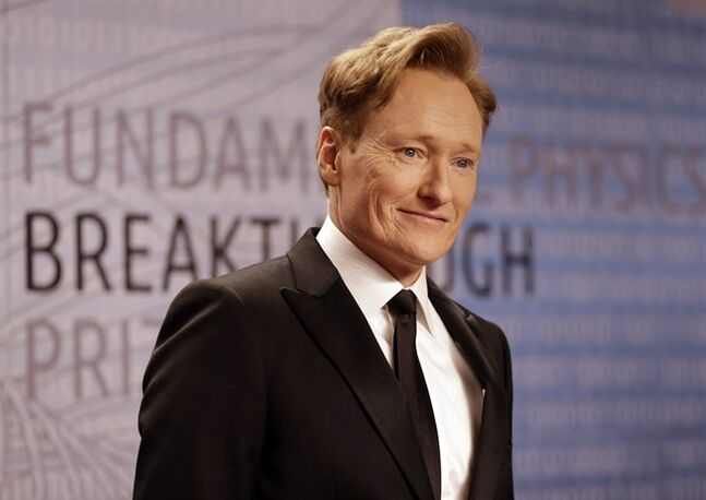 FILE - In this Dec. 12, 2013, file photo, talk show host Conan O'Brien arrives for the Breakthrough Prize in Life Sciences awards in Moffett Field, Calif. TBS says Conan O'Brien will be sticking around with his late-night hour through 2018.
