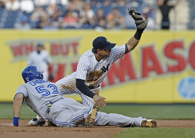 New York Yankees second baseman Brian Roberts, right, shows the ball to the umpire after picking off Toronto Blue Jays' Melky Cabrera (53) in a baseball game at Yankee Stadium in New York, Thursday, June 19, 2014. Cabrera was called safe on the play, but Yankees manager Joe Girardi won the call on an instant replay challenge. (AP Photo/Kathy Willens)