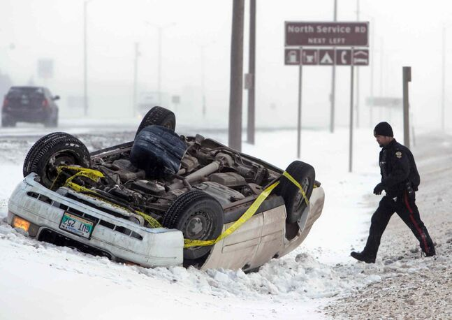 Police attend the scene of a rollover on the Trans-Canada Highway between First Street North and Eighteenth Street North Sunday morning. Winds gusting to 80 km/h, blowing snow and slippery roads contributed to dicey driving conditions across all of southern Manitoba.