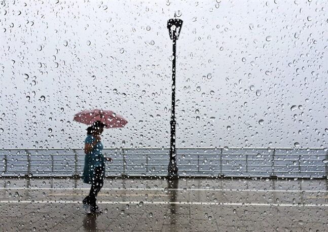 A Lebanese woman takes shelter under her umbrella as she walks on the Corniche, or waterfront promenade, in Beirut, Lebanon, Thursday May 8, 2014. Severe weather and heavy rains affected parts of the Middle East on Thursday including Israel, Jordan and Lebanon. Rains in Israel forced the evacuation of dozens of American tourists who were stranded overnight in a parking lot in the Negev desert, while a new refugee camp for Syrians was flooded in Jordan. (AP Photo/Hussein Malla)
