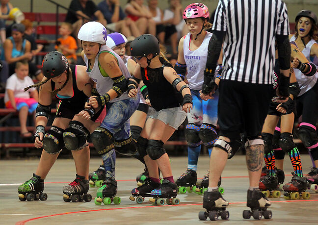 The Frostbite's Tabatha Hamilton pushes her way between a pair of blockers for the Whitewood (Sask.) Bubblegum Girls during Saturday night's junior roller derby match at the Keystone Centre's Optimist Arena.