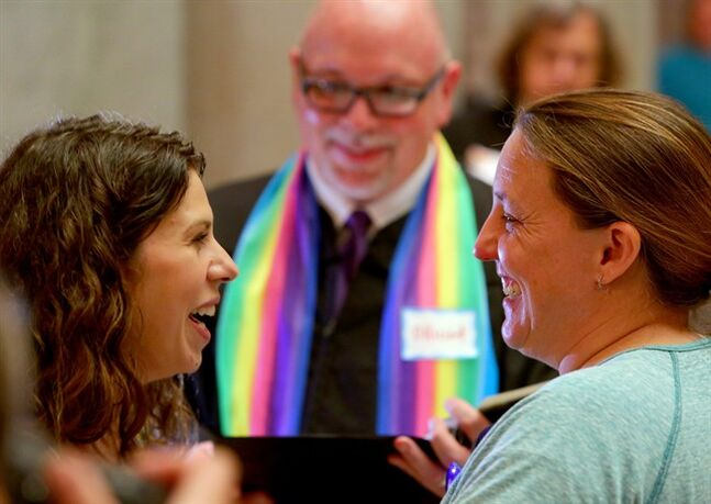 Andria Stock, left, and Chantel Jandak, of Jacksonport, laugh together as they are married by Joey Cole, center, in the rotunda of the Pulaski County Courthouse in Little Rock, Ark. Monday May 12, 2014. (AP Photo/The Arkansas Democrat-Gazette, Stephen B. Thornton)