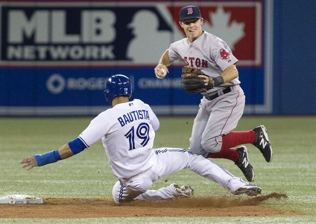 Boston Red Sox Brock Holt gets the force out on Toronto Blue Jays' Jose Bautista at second base but fails to turn the double play on a ground ball hit by Jays' Adam Lind during ninth inning AL baseball game action in Toronto on Monday, August 25, 2014. THE CANADIAN PRESS/Fred Thornhill