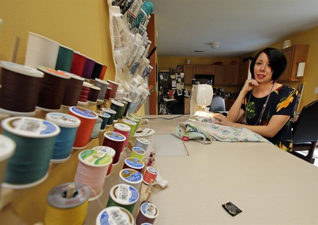 "In this July 16, 2014 photo, Jillian Owens poses with her sewing materials at her home in Columbia, S.C. Since 2010, the 32-year-old Columbia resident has been delving into thrift store racks around the area, taking what some may see as ""ugly"" pieces and whipping them into hip, trendy fashions. (AP Photo/Chuck Burton)"