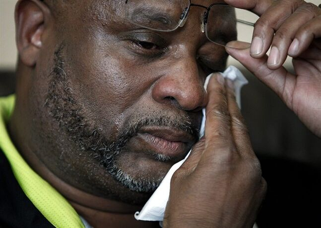 Kenneth Cherry Sr. wipes his face during a news conference in Las Vegas on Saturday, Feb. 23, 2013, regarding the death of his son Kenny Cherry. Kenneth Cherry Jr., was driving a Maserati that was peppered by gunfire before it sped through a red light and smashed into a taxi driven by Michael Boldon carrying passenger Sandra Sutton-Wasmund. All three involved in the crash were killed and the coroner said Cherry died of a gunshot to the chest.