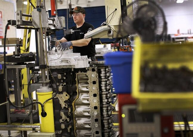 In this March 26, 2014 photo, Jerry Drury installs parts on a truck engine assembly line at Volvo Trucks' powertrain manufacturing facility in Hagerstown, Md. The Federal Reserve releases industrial production figures for May on Monday, June 16, 2014. (AP Photo/Patrick Semansky)