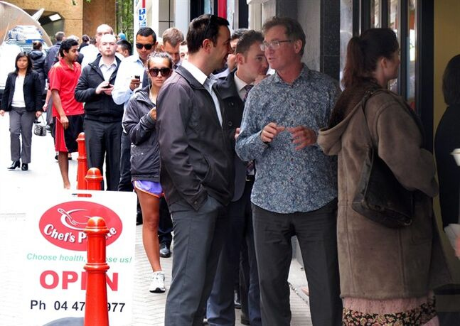 In this Tuesday, Jan. 28, 2014 photo, workers queue to get take-out lunches at the Chef's Palette eatery in Wellington, New Zealand. Five years after the global financial crisis, New Zealand is poised to become one of the first developed nations to begin raising interest rates in response to a thriving economy. The improving economy also seems to be slowing the exodus of residents to Australia, which boasts higher living standards than New Zealand and weathered the financial crisis better than almost every other nation thanks to a mineral boom. (AP Photo/Nick Perry)