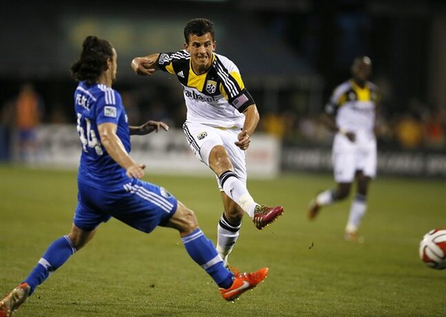 Columbus Crew midfielder Bernardo Anor (7) kicks in his second goal of the night, as Montreal Impact's Heath Pearce defends during the second half of an MLS soccer game Saturday, July 19, 2014 in Columbus, Ohio. The Crew won 2-1. (AP Photo/Columbus Dispatch, Jenna Watson)