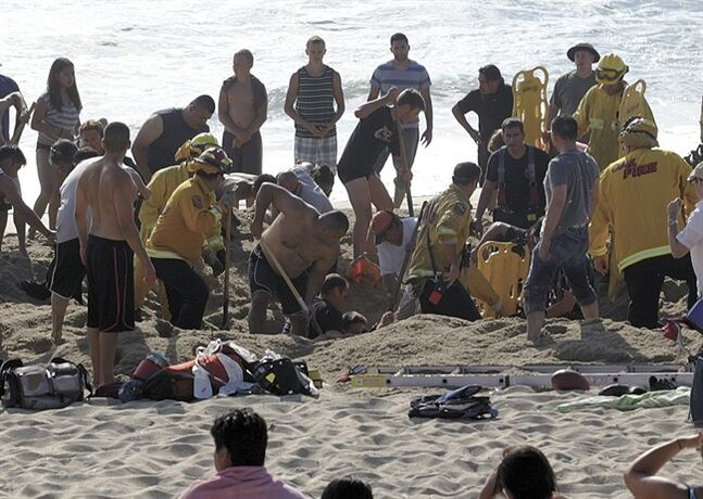 This Monday, July 21, 2014, photo released by the Half Moon Bay Review shows emergency crew workers and volunteers working to rescue a man at Francis State Beach in Half Moon Bay, Calif. Authorities say a young man has died after a hole he dug on a Northern California beach collapsed and trapped him in the sand for at least five minutes. (AP Photo/Half Moon Bay Review, Dean Coppola) MANDATORY CREDIT DEAN COPPOLA/HALF MOON BAY REVIEW