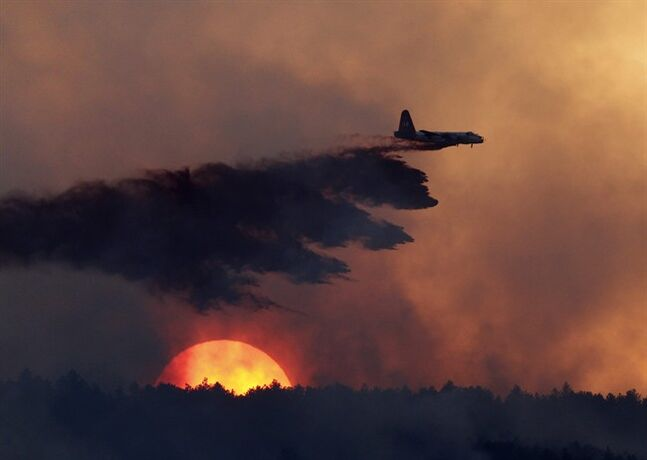 FILE - In this Sept. 12, 2010, file photo, a slurry bomber drops fire retardant on a burning ridge as the sun sets behind it as a wildfire burns west of Loveland, Colo. Global warming is rapidly turning America into a stormy and dangerous place, with rising seas and disasters upending lives from flood-stricken Florida to the wildfire-ravaged West, according to a new U.S. federal scientific report released Tuesday, May 6, 2014. Climate change's assorted harms