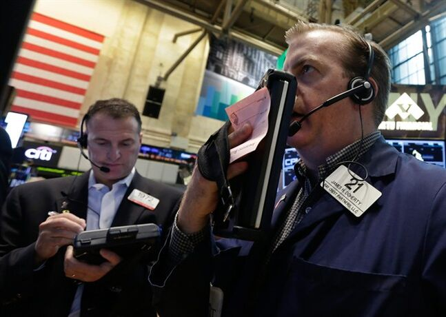 Traders Jonathan Corpina, left, and James Doherty work on the floor of the New York Stock Exchange Friday, May 30, 2014. Two negative reports on U.S. consumers were pushing stocks lower in early trading Friday. (AP Photo/Richard Drew)