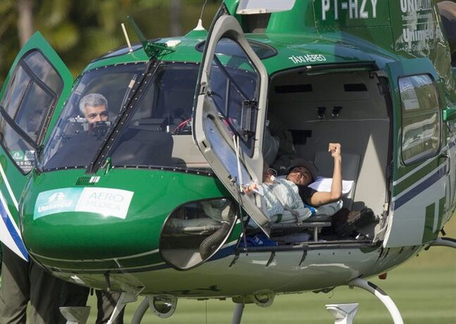 Brazil's Neymar lies inside a medical helicopter at the Granja Comary training center, in Teresopolis, Brazil, Saturday, July 5, 2014. Neymar was airlifted from Brazil's training camp Saturday and will be treated at home for his back injury. Neymar, the biggest football star in Brazil, was ruled out of the rest of the World Cup after fracturing his third vertebra during Friday's 2-1 quarterfinal win over Colombia. (AP Photo/Leo Correa)