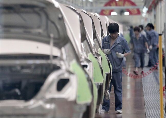 In this June 21, 2012 photo, a worker assembles an automobile at Chinese automaker Geely Cixi Manufacture Base in Cixi, China. THE CANADIAN PRESS/AP, Eugene Hoshiko