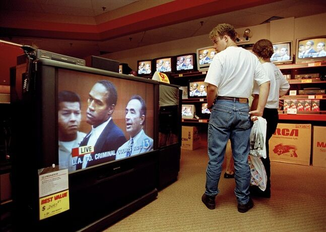 FOR USE SUNDAY, JUNE 8, 2014, AND THEREAFTER - FILE - In this June 20, 1994 file photo, mall shoppers in Tampa, Fla., watch banks of televisions in an electronics store as the arraignment of O.J. Simpson is televised from Los Angeles. The O.J. Simpson trial was labeled the Trial of the Century and a forerunner of today's interactive media. (AP Photo/Chris O'Meara, File)