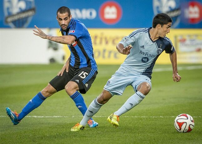 Sporting Kansas City' Igor Juliao, right, steals the ball away from Montreal Impact's Andres Romero during 1st half MLS action in Montreal on Saturday, July 12, 2014. THE CANADIAN PRESS/Peter McCabe