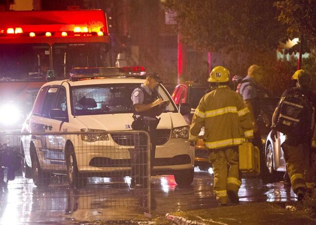 Police and fireman work at the rear of an auditorium where a gunman shot and killed at least one person during the PQ victory rally on September 5, 2012, in Montreal. A hearing on whether Quebec's accused election-night shooter can obtain legal aid will determine how his criminal trial will proceed next year. THE CANADIAN PRESS/Paul Chiasson