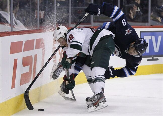 Winnipeg Jets' Evander Kane (9) gets dumped deep in Minnesota Wild's territory by Jared Spurgeon (46) during second period NHL action in Winnipeg on Friday, December 27, 2013. THE CANADIAN PRESS/John Woods