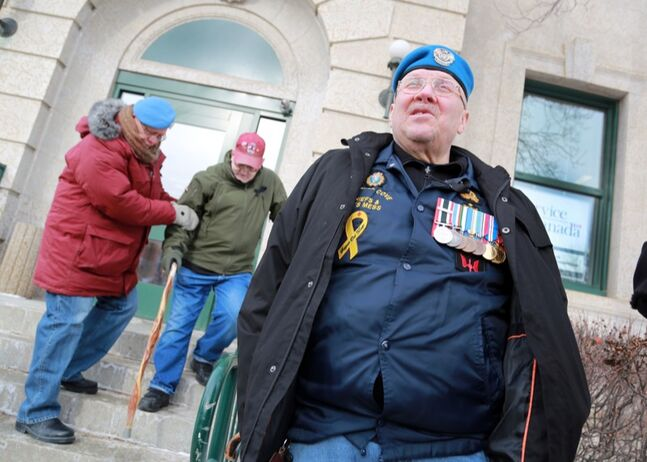 Ed McArthur stands by the Service Canada offices as fellow veteran Tom Cathrow is helped down the stairs by Martin Haller during a protest of federal cutbacks by military veterans at the federal building on Princess Avenue, Friday afternoon. Brandon's Veterans Affairs office was one of 8 cut by the Harper government in a recent decision.